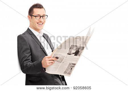 Happy young businessman reading a newspaper and leaning. The newspaper is custom made, pictures are my copyright. You can find them and the necessary Model Releases attached