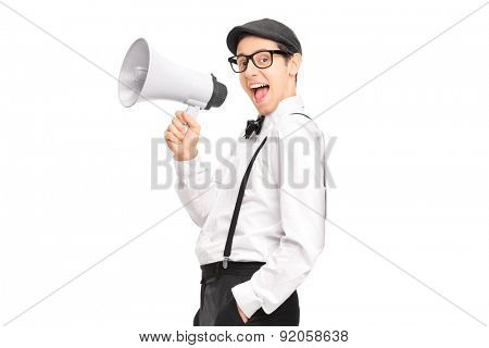 Young artistic man speaking on a megaphone and leaning against a wall isolated on white background