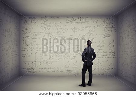 back view of man standing in dark grey room whose walls are painted different formulas