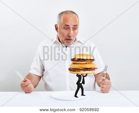 surprised senior man looking at the young man who taking away his plate with burgers