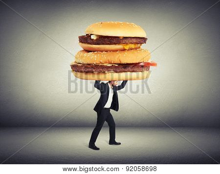 small man in formal wear carrying big sandwiches overhead in empty dark grey room