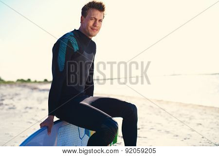 Attractive Surfer Sitting On Edge Of His Surfboard