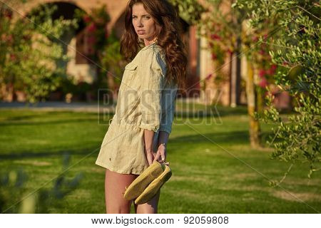 Girl in mowed tuscan hay field near garden in Toscana, Italy