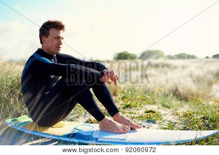 Surfer Sitting On His Board On A Sand-dune