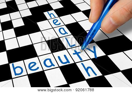 Hand filling in crossword - health and beauty