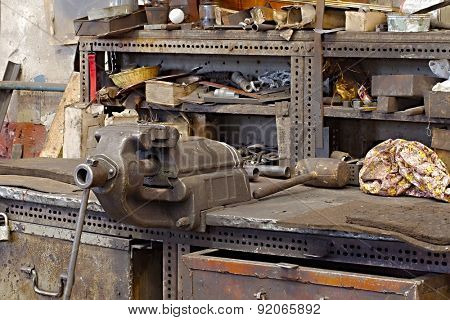 Messy workshop table with vise and old tools