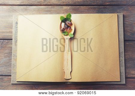 Open recipe book with spoon on wooden background