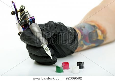 Hand of tattoo artist with tattoo machine and colorful ink isolated on white