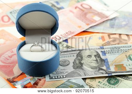 Wedding ring in box  on banknotes background. Marriage of convenience