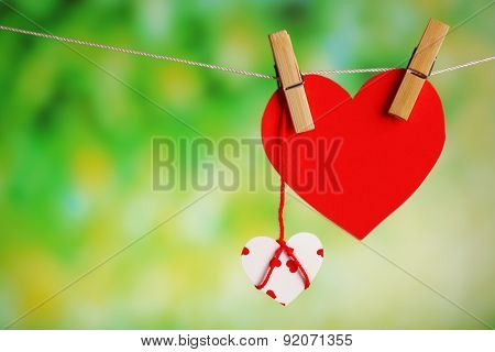 Paper hearts hanging on rope on bright background