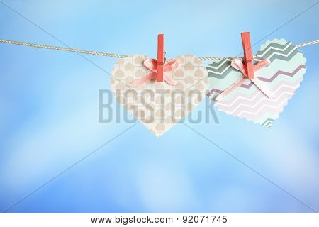 Hearts hanging on rope on bright background