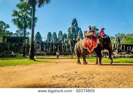 Tourists ride elephant on howdah chair, Cambodia