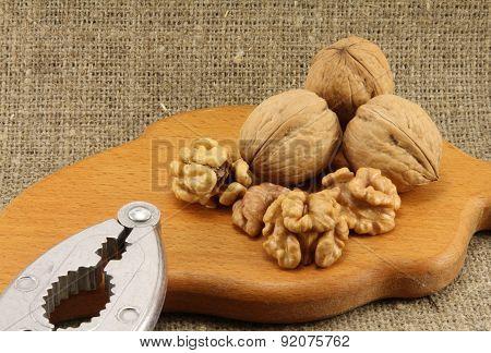 Walnuts On A Wooden Board (cutting Board) With A Nutcracker