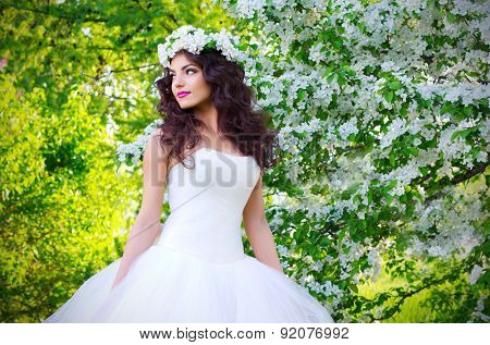 Young bride on the background of blooming apple trees