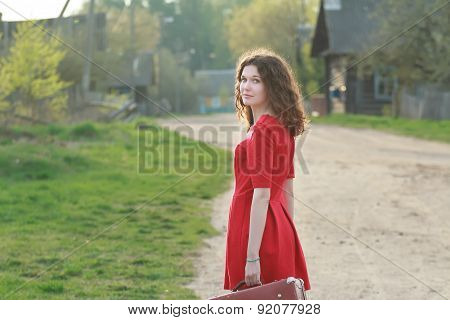 Young Woman In Feminine Red Dress Looking Over Her Shoulder During Her Vintage Travel