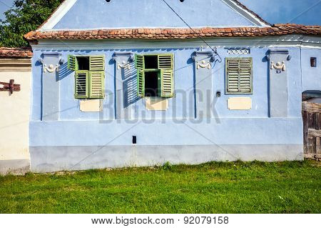 Blue Painted Traditional House With Green Shutters From Viscri Village In Transylvania, Romania