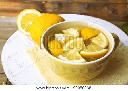 Still life with lemon juice and sliced lemons on wooden stand, closeup