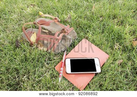 Flip-flops With Book,mobile,pencil In The Grass