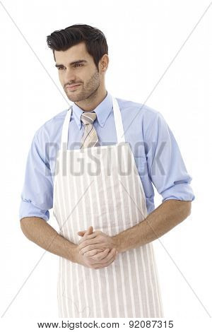 Portrait of handsome chef in apron, looking away.