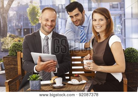 Happy, smiling caucasian businesswoman and businessmen enjoying success at breakfast, Suit and tie, tablet computer, looking at camera, outdoor.
