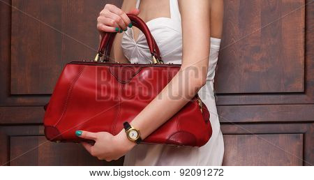 Fashionable sexy woman posing in elegant white dress with red leather handbag in hands