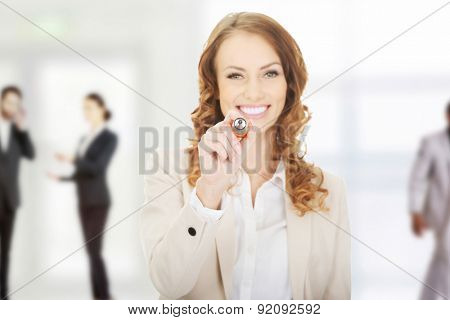 Attractive businesswoman writing with oversized pen.