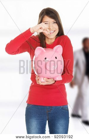 Happy student woman putting a coin to piggybank.