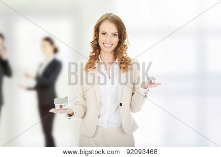 Smiling businesswoman compares two house models.