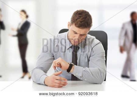 Handsome businessman checking time on his watch.