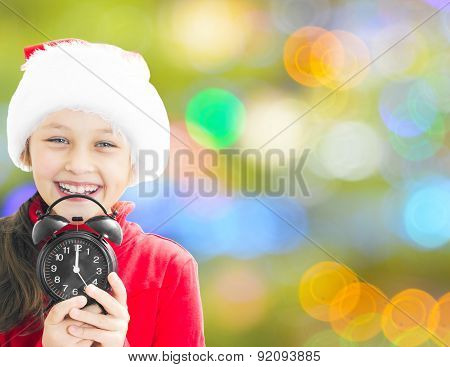Girl In Santa Claus Hat Holding Alarm Clock Showing Twelve O'clock