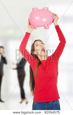 Shocked young student woman with piggybank.