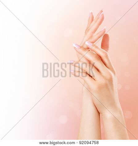 Beautiful Female Hands. Spa and Manicure concept. Woman hands with french manicure. Soft skin, skincare concept. Beauty nails. over beige background