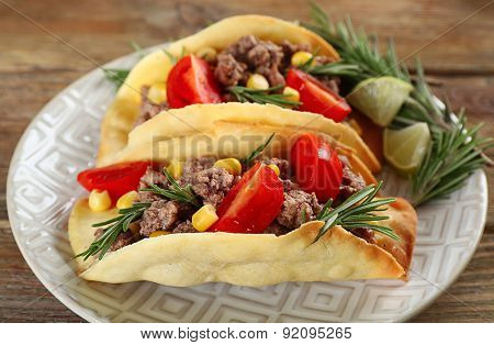 Mexican food Tacos in plate on wooden table, closeup