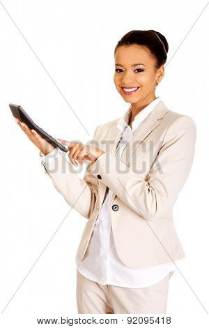 Smiling african business woman counting on calculator.
