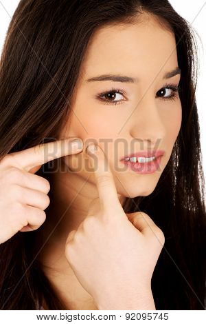 Unhappy teenage woman squeezing pimple.