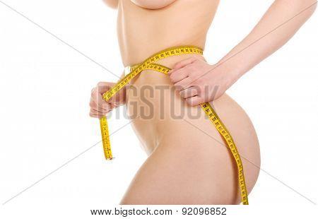 Slim undressed woman measuring her waist.