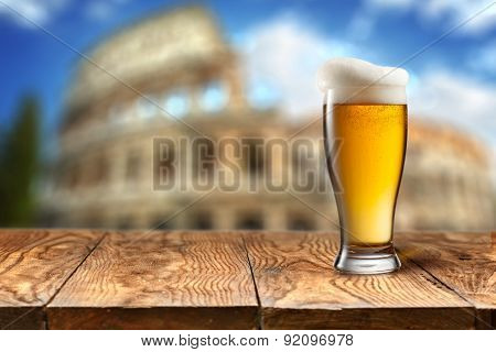 Glass of beer on wooden table with Colosseum in Rome on background with natural bokeh