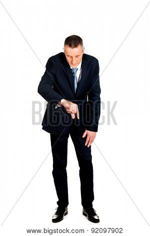 Full length businessman showing small size with fingers.