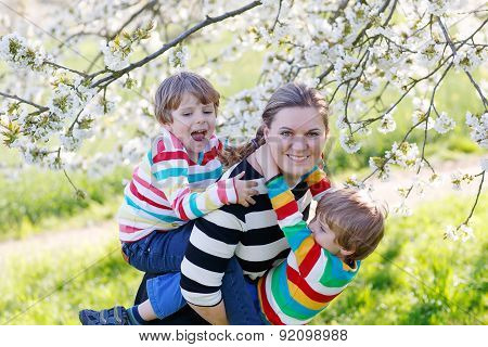 Young Mother And Two Little Twins Boys Having Fun In Blooming Garden
