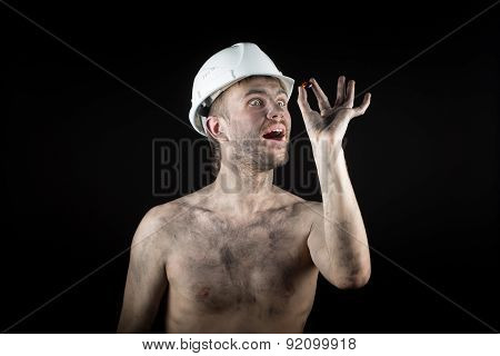 Happy dirty worker in helmet. gemstone,