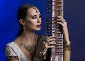 image of indian blue  - Beautiful Young Indian Woman in Traditional Sari Clothing with oriental jewelry Bridal Makeup Playing the Sitar - JPG