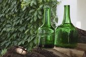 foto of green wall  - Antique bottles of green glass are on the chopping wood - JPG