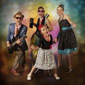stock photo of rockabilly  - Rockabilly family band playing music and singing on a black background with glowing lights - JPG