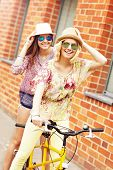 pic of tandem bicycle  - A picture of two girl friends riding a tandem bicycle in the city - JPG