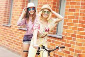 stock photo of tandem bicycle  - A picture of two girl friends riding a tandem bicycle in the city - JPG