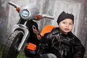 image of tricycle  - Adorable toddler wearing a leather jacket and bandanna and sitting next to a toy tricycle - JPG