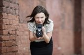 stock photo of young woman posing the camera  - Woman photographer with an old vintage camera in hand on a brick wall background - JPG