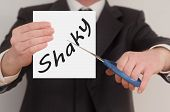 image of shaky  - Shaky man in suit cutting text on paper with scissors - JPG