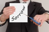 image of sorrow  - Sorrow man in suit cutting text on paper with scissors - JPG