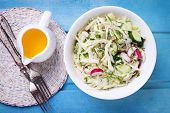 stock photo of grated radish  - Salad from cabbage herbs cucumber onion and radish in bowl on blue wooden background - JPG